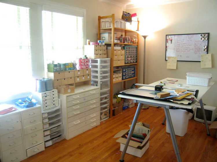 organized craft room with storage, drawers and work table.