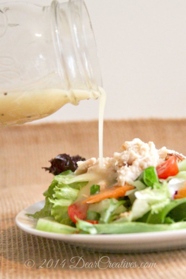Salad dressing being poured onto a salad_