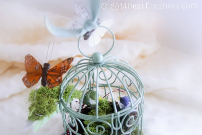 Green bird cage close up with close up of butterflies