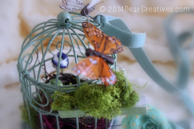 bird cage with velvet ribbon and butterflies and moss