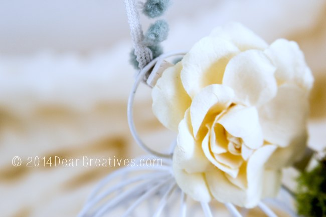 close up of fabric flower on top of mini bird cage