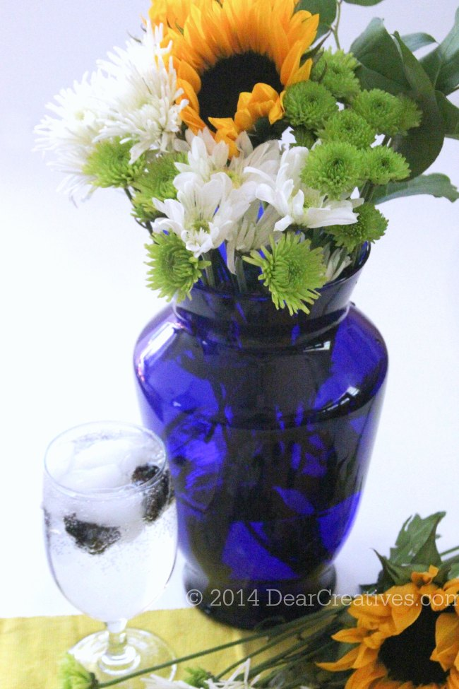 flowers in a vase next to a glass of sparkling water_