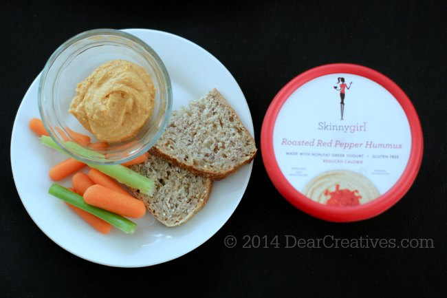 Hummus in a bowl on a plate with veggies and Skinnygirl Roasted Red Pepper Hummus next to skinnygirl hummus