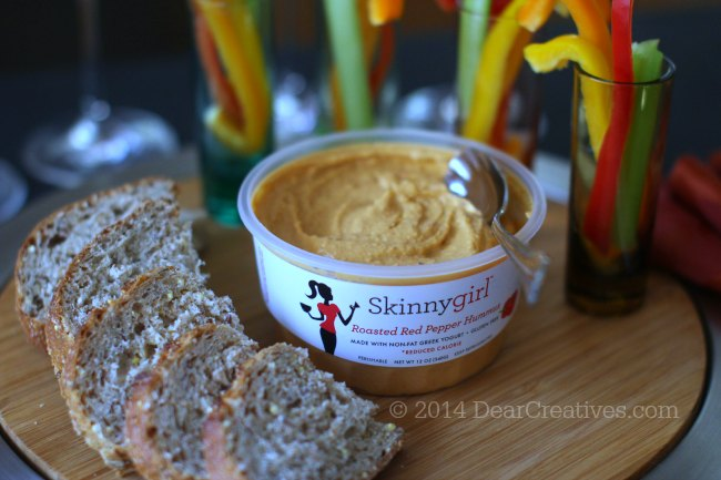 Opened package of skinnygirl roasted red pepper hummus on an appetizer serving tray