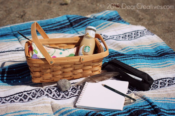 Drawing Supplies and iced coffee on a beach blanket