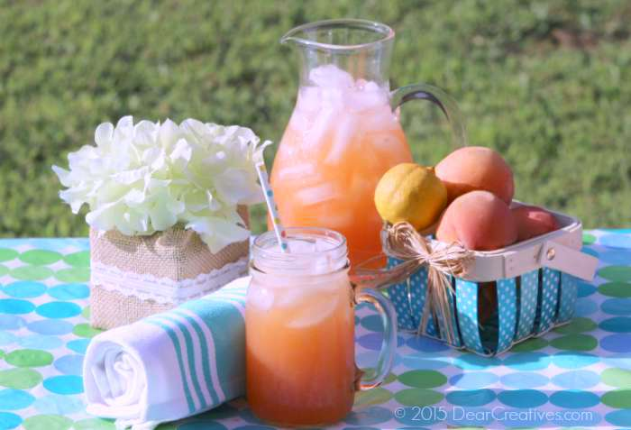 Peach Strawberry Lemonade outside on a picnic table - a homemade lemonade with peaches and strawberries. This is an easy drink recipe to make. DearCreatives.com