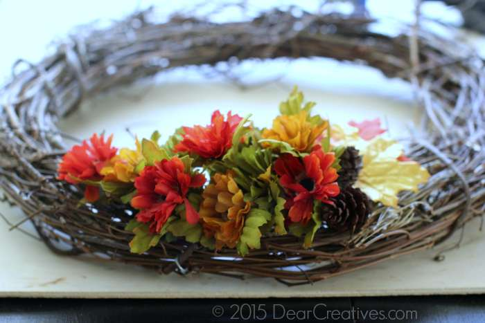 Making floral wreath flowers and pine cones on side of wreath