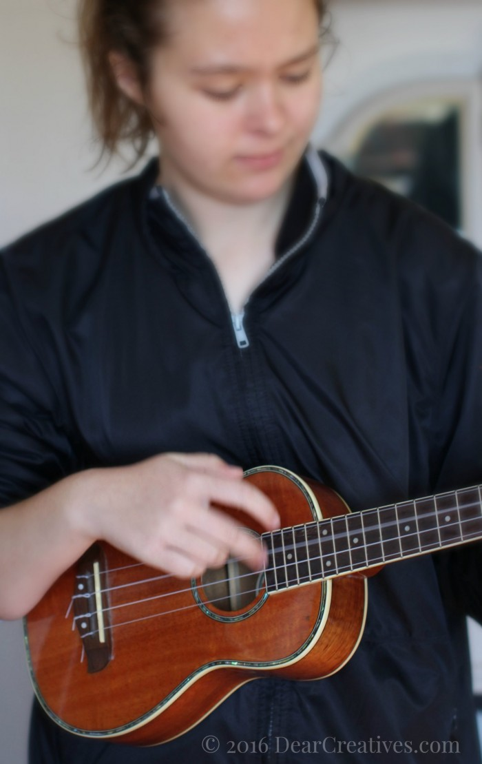 Teen playing a Ukulele