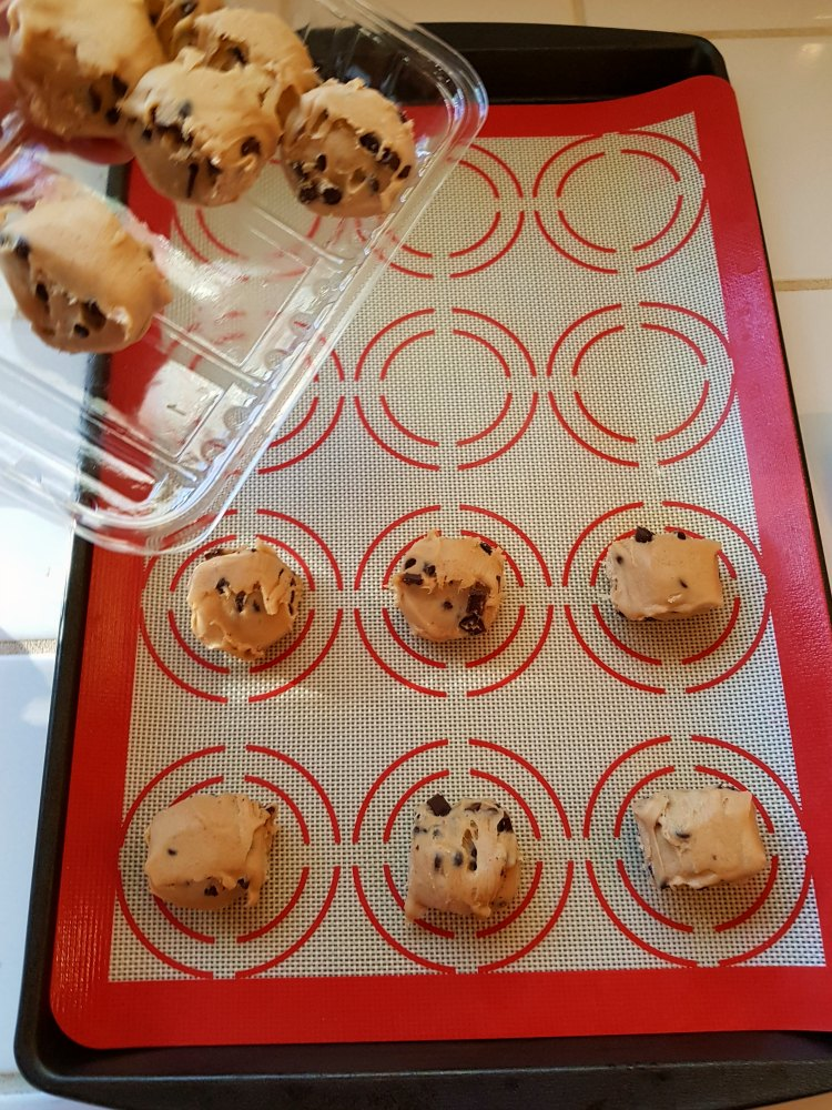 chocolate chip cookie dough being put onto a cookie sheet for a Halloween cookies recipe