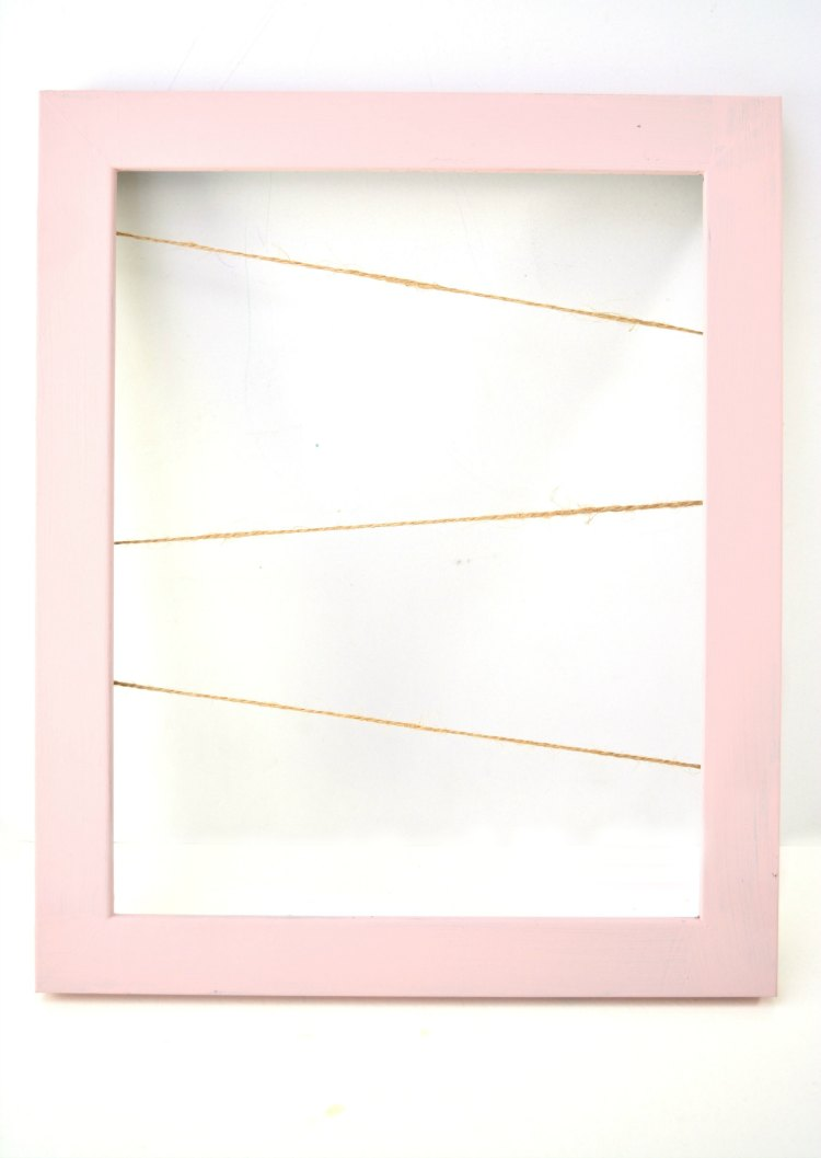 Painted wood frame with pink paint, and string strung for hanging hearts for Valentine's Day Craft project DearCreatives.com