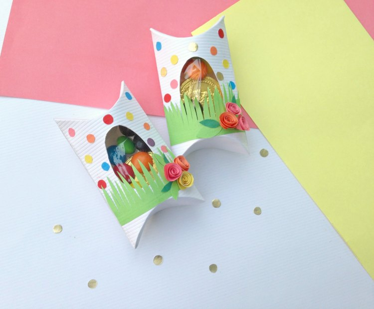 Easter treat boxes with grass, flowers, and colorful dots with candy inside See DIY at DearCreatives.com.