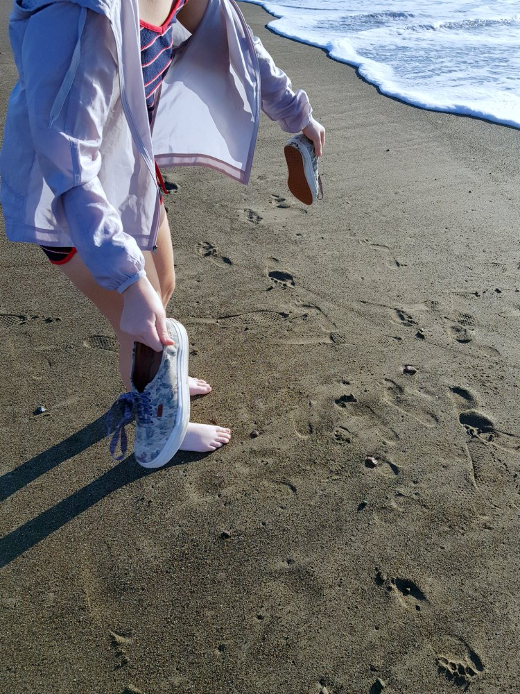 knocking the sand off tennis shoes at the beach to put into a bag