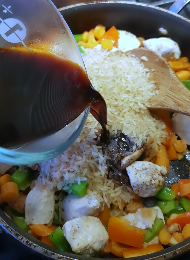 soy sauce being added to chicken, vegetables, and rice for a one pan meal. DearCreatives.com