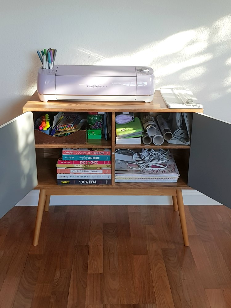 Inside storage of Oslo Table Console storage cabinet. Filled with office supplies, cooking books, and craft supplies. DearCreatives.com