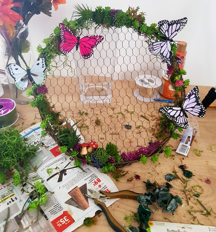finishing touches to a grapevine wreath with chicken wire with succulents, moss, butterflies, and mushrooms. See how to decorate a wreath at DearCreatives.com