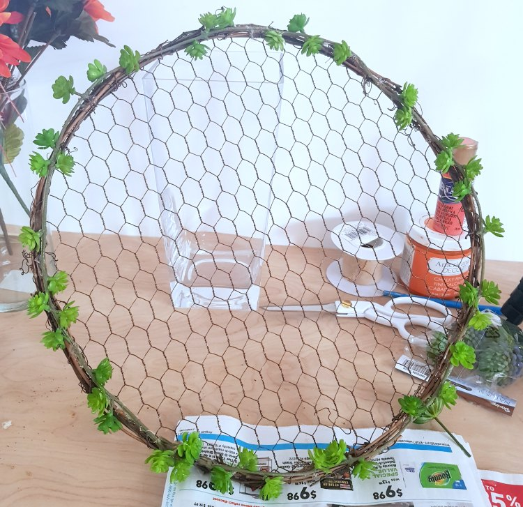 succulent garland placed around a grapevine wreath with chicken wire. Full wreath diy at dearcreatives.com