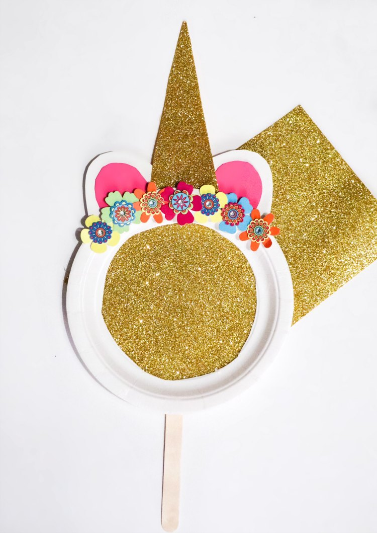 Unicorn Mask made from a paper plate, and craft supplies. This is an easy kids craft to make. If you and your kids love unicorn crafts see this unicorn craft and more at DearCreatives.com