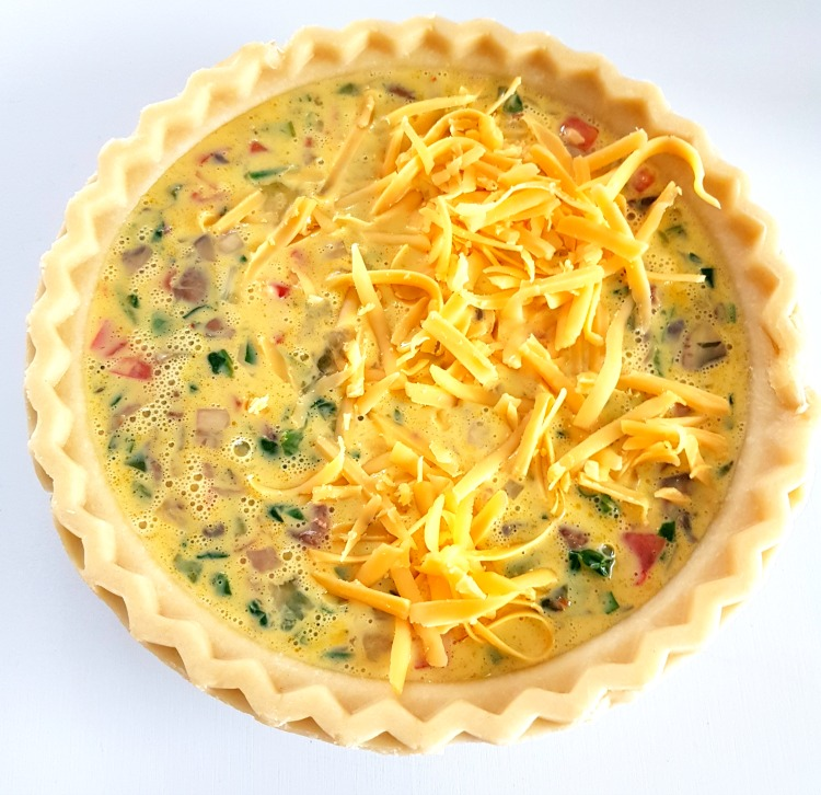 adding cheese to top of cheese quiche ready to be baked in the oven © DearCreatives.com