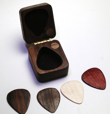 Four wooden guitar picks, and storage case