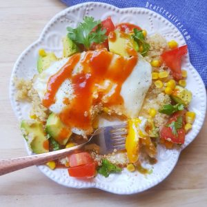 Southwest quinoa egg breakfast bowl with a fork in food, ready to eat the breakfast bowl. DearCreatives.com