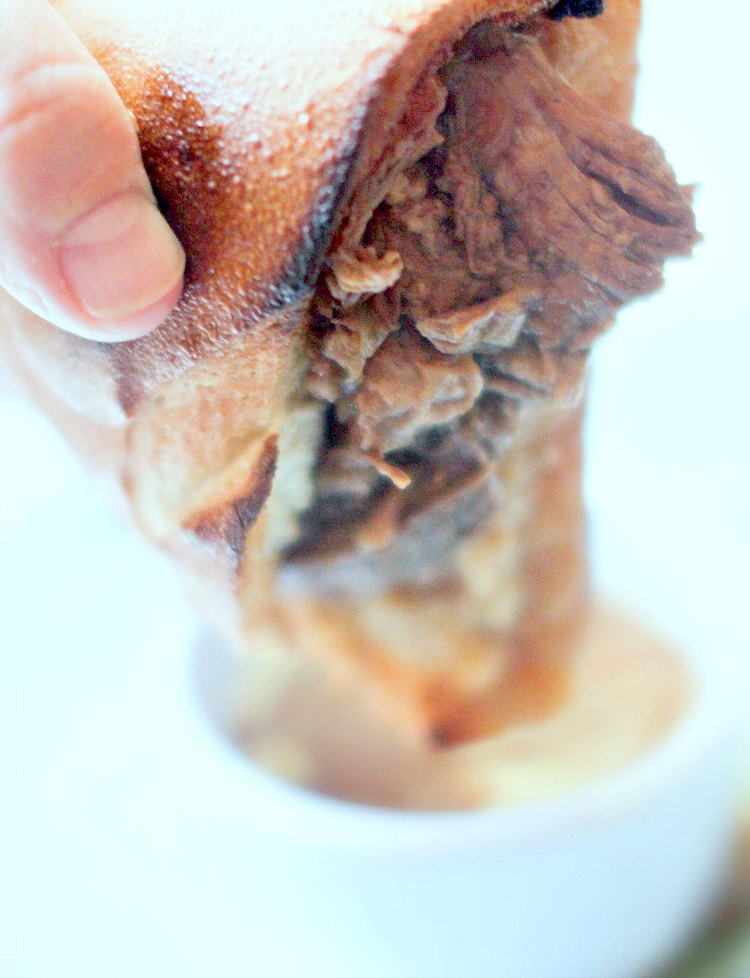 French Dip Sandwiches - holding a beef dip sandwich after dipping it in au jus sauce DearCreatives.com