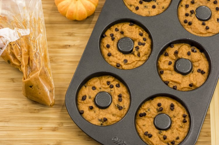 Pumpkin donuts dough added to the donuts baking pan for baking pumpkin donuts. Pumpkin Chocolate Chip Donuts Paleo Recipe at Dearcreatives.com