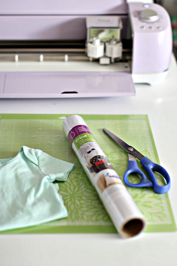 Cricut cutting machine, iron on material, baby onsie, scissors, and cutting mat to make iron on onsies DearCreatives.com