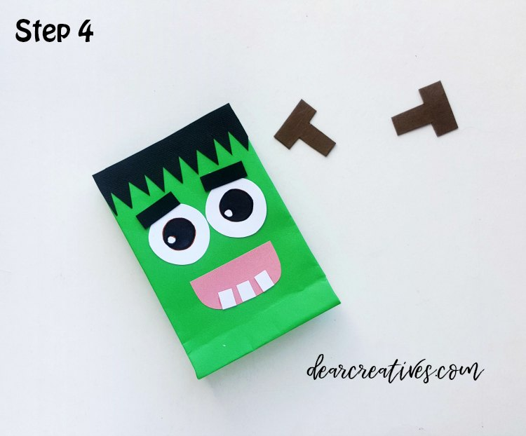 Frankenstein Treat Bag step (4) Glue the mouth and then glue the 3 square patterns (tooth) along the bottom side of the mouth's inner part. DearCreatives.com