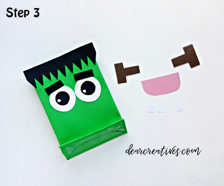 Halloween Treat Bag step (3) Glue the eyes and the eyebrows right below the hair; keep a gap between the hair and the eyes. DearCreatives.com
