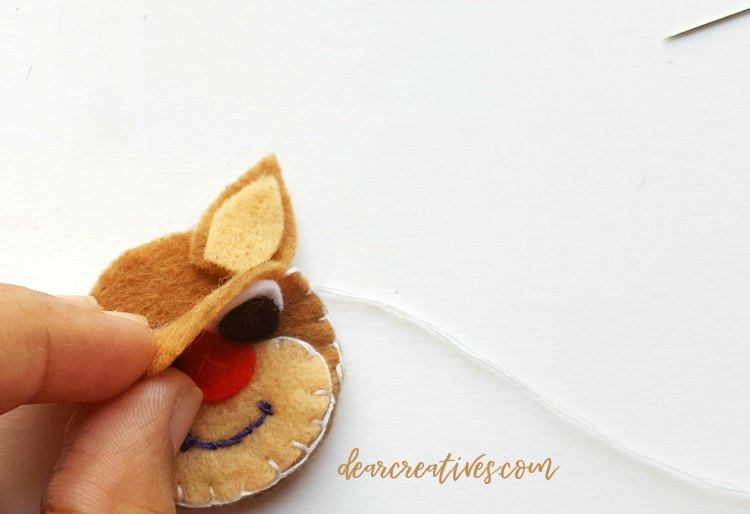 for step (7) place ears in between front of reindeer head and place on inside back of the deer head. DearCreatives.com #reindeerornament