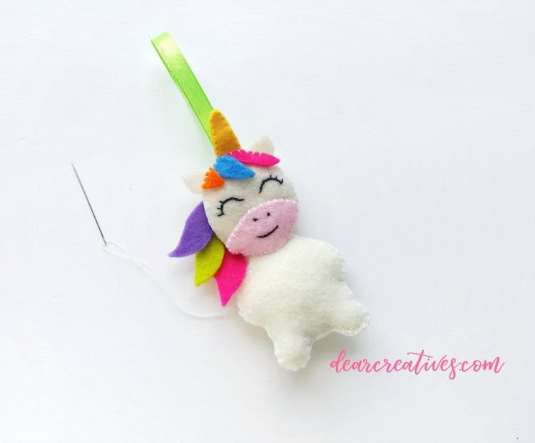 Finishing up sewing and completing step (17) of the unicorn ornament grab free pdf unicorn template and instructions at DearCreatives.com