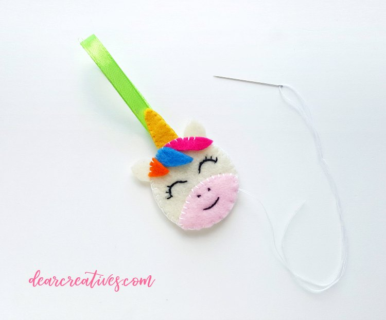 Sewing the unicorns hair on the felt face. See the entire felt craft diy at DearCreatives.com