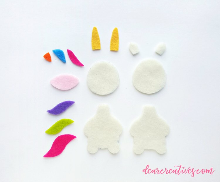 felt unicorn cut out of felt ready to be made into a Christmas ornament. diy with free printable unicorn template at DearCreatives.com