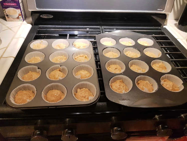 Muffins in muffins baking pans ready to have the crumb topping added before baking in the oven. DearCreatives.com