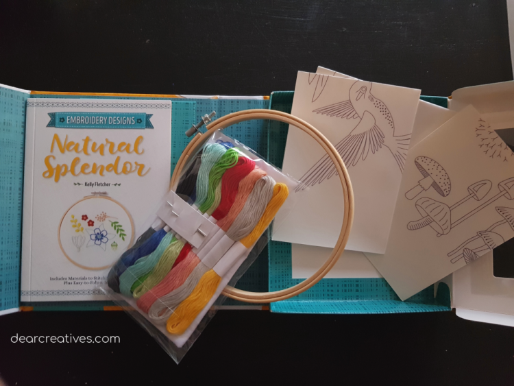 Open embroidery kit showing embroidery patterns, embroidery threads, hoop, and fabric that comes with 12 designs - DearCreatives.com