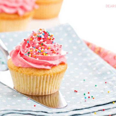 Vanilla Cupcakes with pink frosting and colorful sprinkles