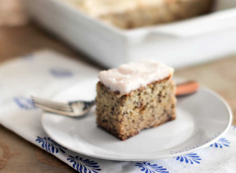 banana cake with cream cheese frosting on a plate with a fork - banana cake recipe at DearCreatives.com #bananacake