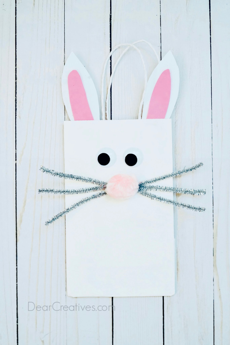 decorated bunny paper bag laying on a flat surface. Instructions with images at DearCreatives.com #crafts #bunnybag #bunnypaperbag #dearcreatives