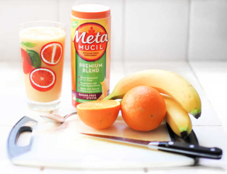 smoothie with oranges, banana and fiber in a glass. Fresh fruit on a cutting board- DearCreatives.com