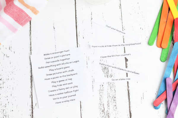 Cutting out the kids activity list to be glued onto the popsicle sticks. See full craft instructions and free printable at DearCreatives.com