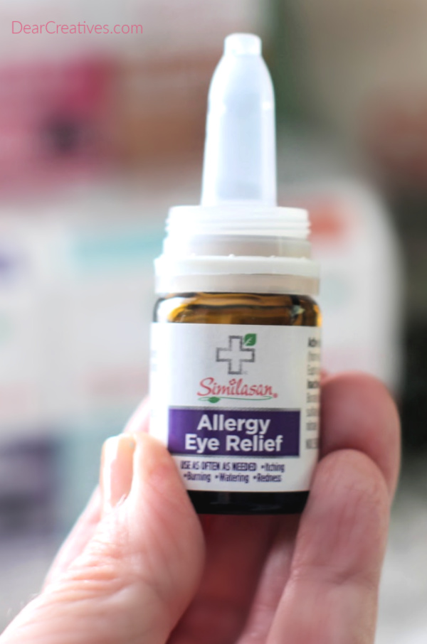 Holding up a bottle of allergy relief medicine. Similasan Allergy Relief. Tips for fighting allergies. DearCreatives.com