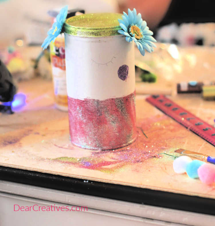 Begin to glue on the faux flowers to your can or jar. Unicorn DIY at DearCreatives.com