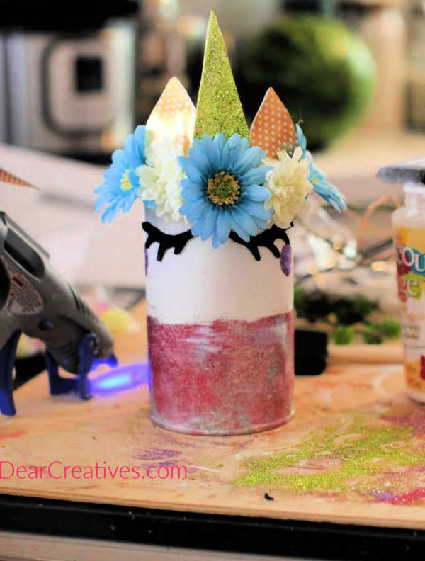 Cut out unicorn felt eyes or purchase them and add them to your unicorn can or jar with a hot glue gun or strong glue. Full instructions at DearCreatives.com
