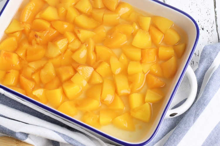 Peaches in syrup in a 9 x 13 baking dish for a dump cake recipe. Grab this easy cake recipe at DearCreatives.com