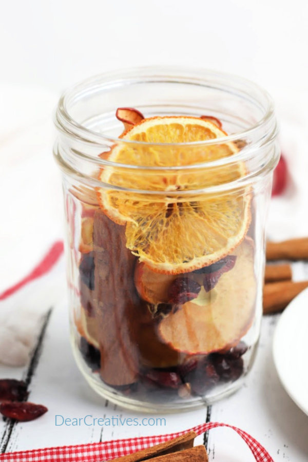 mason jar with dried cranberries, oranges, apples, cinnamon sticks... See how to make a simmering pot gift in a jar. DIY potpourri - DearCreatives.com