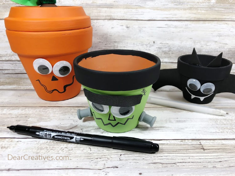 Adding faces with a permanent marker to the clay pot Halloween characters; Frankenstein, Jack-O-Lantern and Bat. Halloween craft tutorial at DearCreatives.com