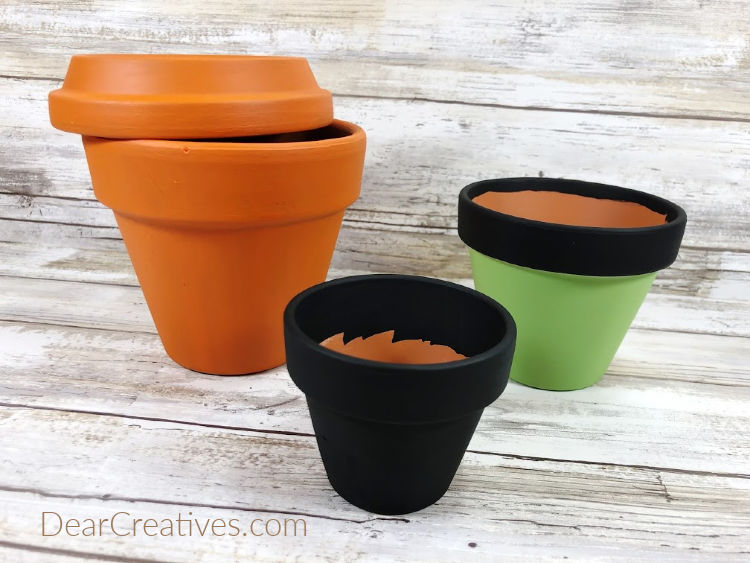 Begin to paint the clay pots with acrylic paints. See all the steps for this Halloween clay pot craft at DearCreatives.com