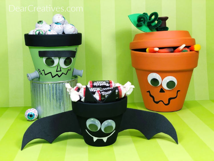 Clay pots painted and decorated for Halloween. Make a Jack-O-Lantern, Frankenstein, and a Bat! DearCreatives.com
