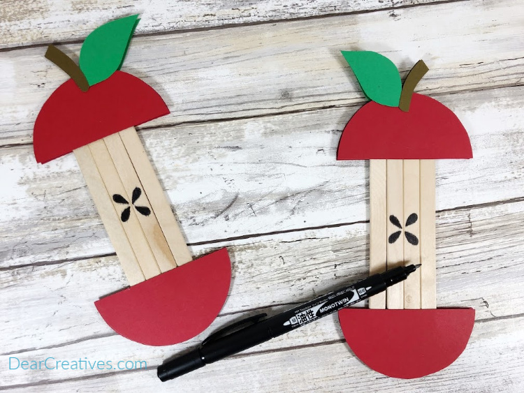 Popsicle Stick Apple Craft - adding on the apple seeds to the apple stick. For instructions and printable apple pattern go to DearCreatives.com
