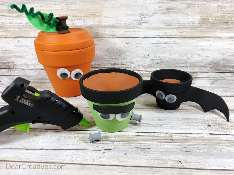 Attach all features to clay pots with a glue gun and glue sticks. Use photo for placement. Step 5 of the step by step instructions with images for making a Frankenstein, Jack-O-Lantern and a Bat from clay pots